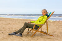 Dutch woman sits in beach chair by the sea