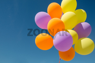 close up of colorful helium balloons in blue sky