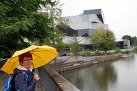 Frau mit gelbem Regenschirm vor Science Center Heilbronn am Neckar