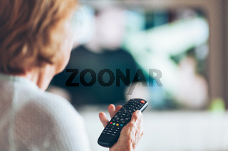 Senior woman with remote control watching television