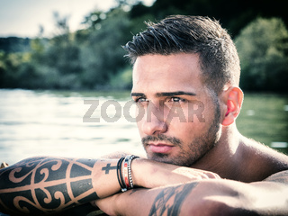 Handsome tattooed young man in boat
