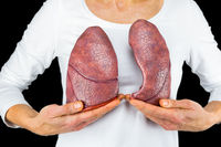 Woman holds two lungs at white body