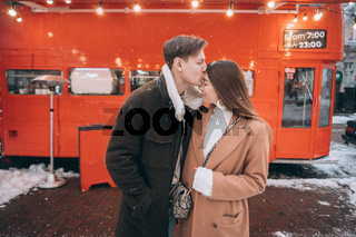 beautiful young couple posing by the old bus
