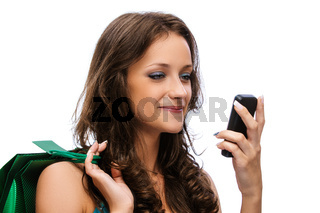 smiling beautiful woman with dark hair in blue dress with green bag and phone