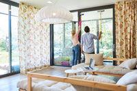 Junges Paar beim Hausputz im Wohnzimmer