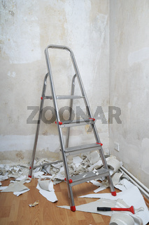 empty room with bare walls ladder and old wallpaper scraps on floor during redecoration