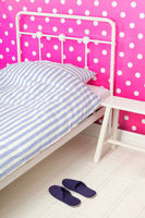 Pink bedroom with bed and slippers