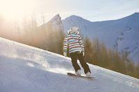 Female snowboarder in sun flare