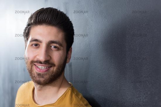Handsome young man smiling on black background. Studio shot.