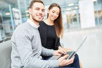 Junges Paar im Flughafen Terminal mit Laptop