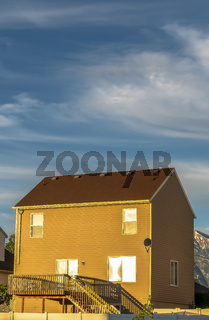 Vertical frame Homes with horizontal wall siding against mountain and cloudy sky on a sunny day