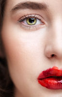 Closeup macro portrait of female face. Human woman half-face with unusual beauty makeup. Girl with perfect skin, green pistachio colour eyes and scarlet red lips make-up.