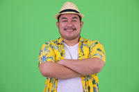 Happy young overweight Asian tourist man smiling with arms crossed