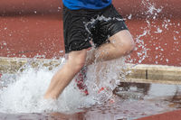 Runner in a steeple chase water bake on a running track