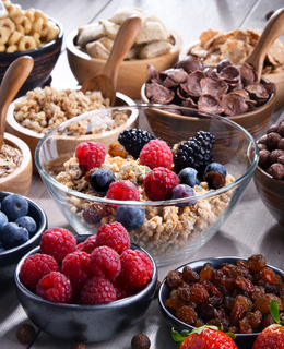 Composition with different sorts of breakfast cereal products and fresh fruits.