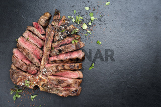 Barbecue dry aged wagyu porterhouse steak sliced and decorated with spice and herbs as top view on a black slate slab with copy space right