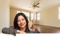 Hispanic Woman with Thumbs Up In Empty Room of House