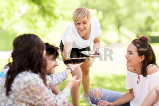 happy friends sharing pie at picnic in summer park