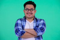 Happy young overweight Asian hipster man smiling with arms crossed