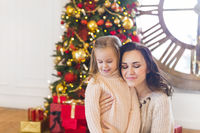 Cheerful mom and her cute daughter by the Christmas tree