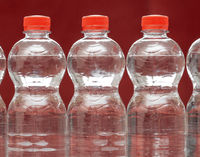 Row of water bottles, bubbling spa red, recycling environment concept
