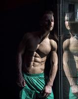 Handsome shirtless muscular man posing in gym