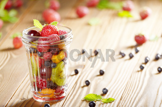 Assorted berries in mason jar on kitchen wooden table