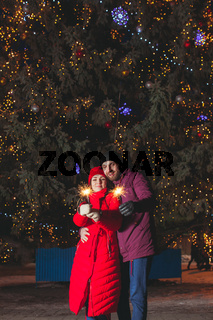 Man and woman embracing under large fir tree