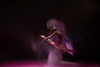 Woman jumping gracefully in color dust cloud