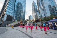 Senior women practising square dancing in front of skyscrapers