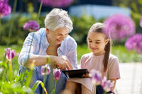grandmother and girl with tablet pc at garden