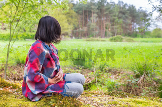 Young woman sits in forest near meadow