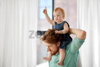 father carrying his little baby daughter on neck