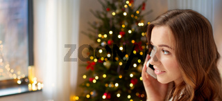 happy young woman calling on smartphone at home