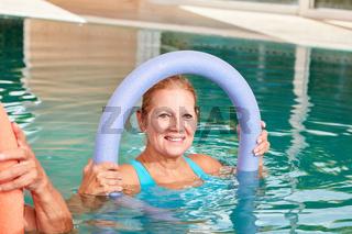 Alte Frau mit Schwimmnudel im Pool