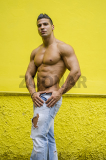 Muscular man shirtless against yellow wall