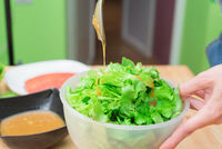 Female hands adding sauce to lettuce from lettuce leaves. Home kitchen. Tasty healthy and healthy food