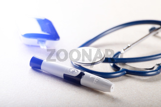 Personal blood glucose meter and lancet with stethoscope on the table