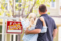 Caucasian Couple Facing and Pointing to Front of Sold Real Estate Sign and House