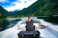 Woman driving a motor boat. Geiranger fjord, Beautiful Nature Norway.Summer vacation.