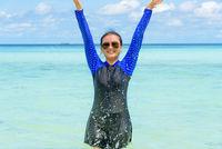 Happy asian teen girl play splashing water in the sea