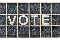 Wooden word VOTE on black sand