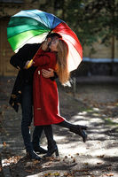 Young people walking in park under colorful umbrella