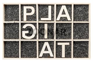 Word PLAGIAT unusual spelling on black sand