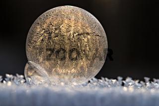 gefrorenen Seifenblase vor dunklem Hintergrund. Untergrund ist Schnee