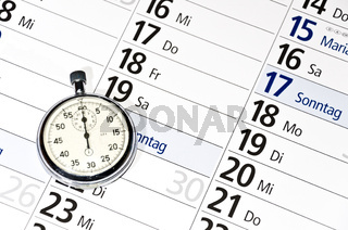 Stopwatch lying on calendar (with captions of the days of the week in German)