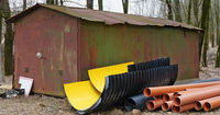 New plastics sewer pipes and gutters lie near a rusty metal rustic shed.