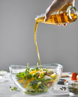A girl's hand pours oil into a freshly prepared vegetable salad in a bowl on a gray background with copy space. Healthy food