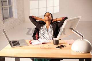 Happy businesswoman sitting at her working place and relaxing.