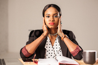 African american young businesswoman sitting by the table in dusiness clothes and holding her hands near her head.